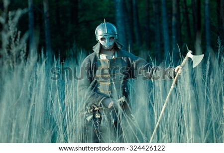 Medieval slav warrior man wearing in ancient armor with axe. - stock photo