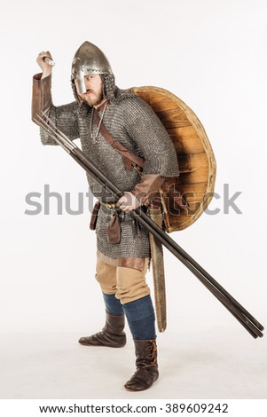 medieval slavic soldier standing and ready for a fight with spear, helmet and hauberks. image on white studio background. historical concept. - stock photo