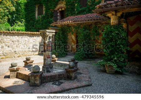 Medieval square with dry fountain and arcades in Grazzano Visconti, Italy