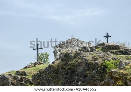 Medieval stone orthodox chapel exterior and christian cross on mountain hill - stock photo