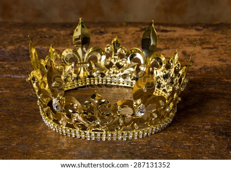 Medieval style golden crown on antique wooden background