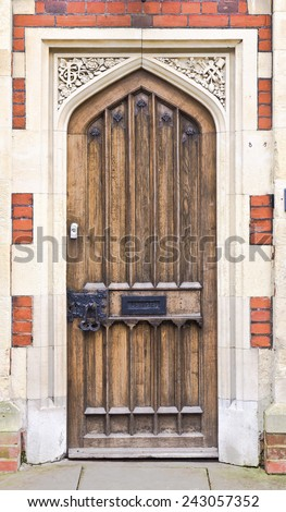 Medieval style wooden door in a brick building - stock photo