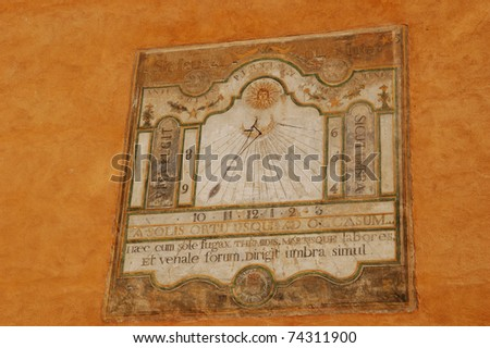 Medieval sun-dial painted on building wall in Briancon, France, isolated on orange background - stock photo