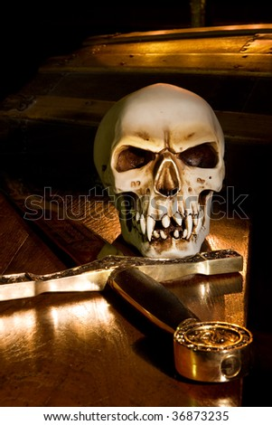 Medieval sword and spooky skull lit by candles