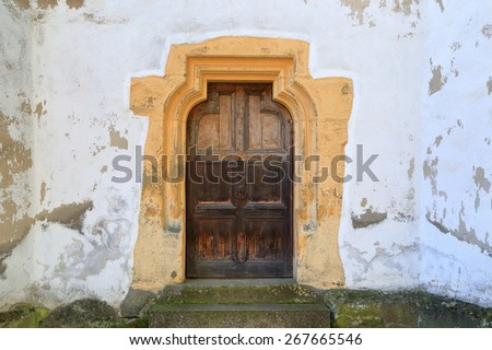 Medieval wall with aged wooden door of an old church of Prejmer, Transylvania, Romania - stock photo
