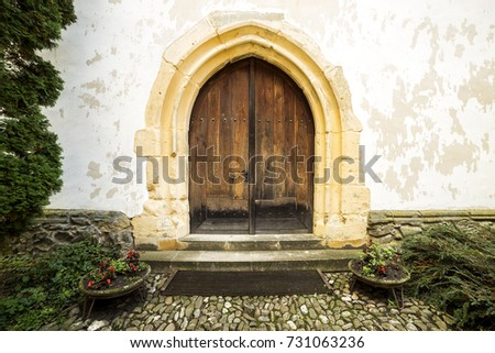 Medieval wall with aged wooden door of an old church of Prejmer, Transylvania, Romania