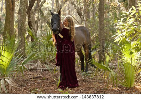 medieval woman in dress with horse in forest - stock photo