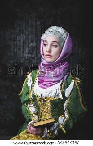 Medieval woman She is holding a book and a crucifix. Pray. In the old beautiful yellow-green dress. Historic image. Gothic. Europe