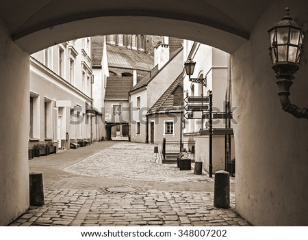 Medieval yard in old Riga city - capital and largest city of Latvia, a major commercial, cultural, historical and financial center of the Baltic region  Image toned for inspiration of retro style