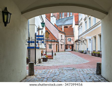 Medieval yard in old Riga city. Riga is the capital and largest city of Latvia, a major commercial, cultural, historical and financial center of the Baltic region - stock photo