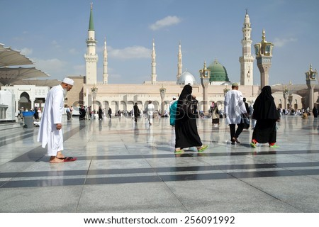 MEDINA, KINGDOM OF SAUDI ARABIA (KSA) - JAN 30: In the prophetic mosque courtyard, walking Muslims on January 30, 2015 in Medina, KSA. Mosque is visiting hundreds of thousands of Muslims every year. - stock photo