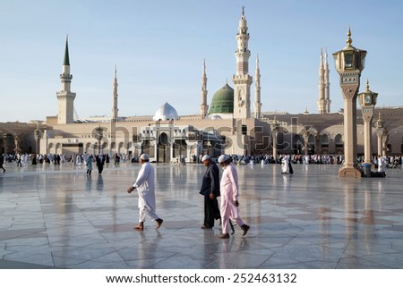 MEDINA, KINGDOM OF SAUDI ARABIA (KSA) - JAN 31: Muslims marching in front of the mosque of the Prophet Muhammad on January 31, 2015 in Medina, KSA. Prophet's tomb is under the green dome. - stock photo