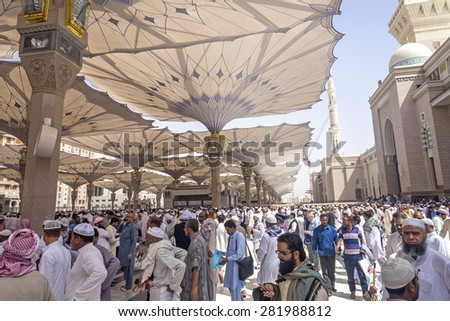 MEDINA - MARCH 06 : Pilgrims walk out after praying at Nabawi Mosque compound on March 06, 2015 in Medina, Kingdom of Saudi Arabia. Nabawi mosque is the second holiest mosque in Islam. - stock photo
