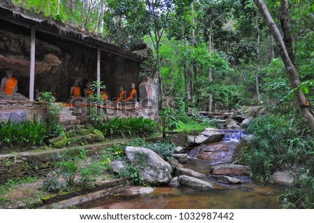 Meditating Buddhist monk sculptures near Buddhist temple surrounded by tranquil peaceful tropical nature, jungle, greenery, waterfall, stream flowing over rocks in mountains. Chiang Mai, Thiland