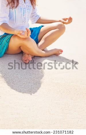 meditating on a beach - a faceless closeup - stock photo