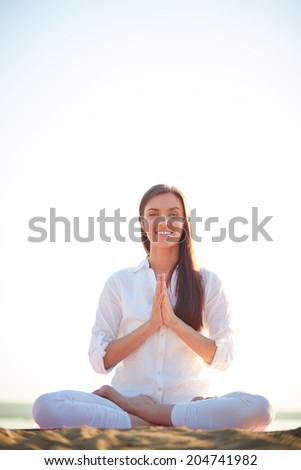 Meditating woman sitting in pose of lotus against clear sky outdoors - stock photo