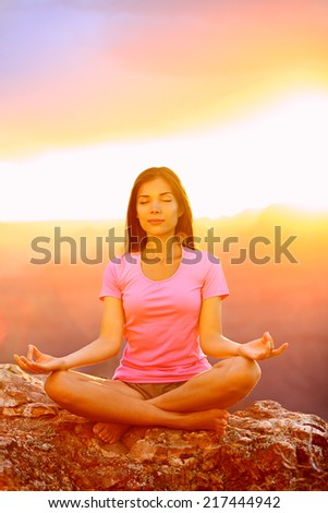 Meditating yoga woman at sunset in Grand Canyon. Female model meditating in serene harmony in lotus position. Healthy wellness lifestyle image with multicultural young woman. From Grand Canyon, USA. - stock photo