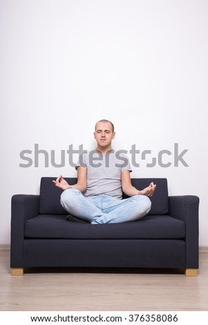 meditation concept - tired man sitting on sofa in yoga pose in living room - stock photo