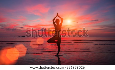 Meditation girl on the sea during sunset. Yoga silhouette. Fitness and healthy lifestyle.
