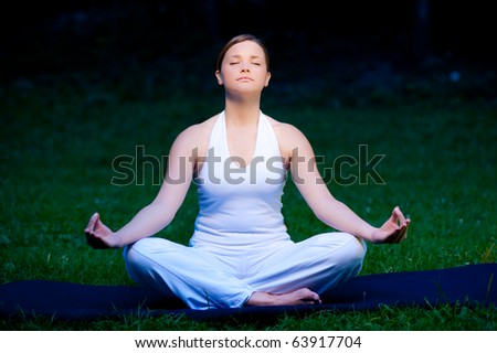 Meditation in nature - Cute young girl meditates outdoor on a green grass field - stock photo