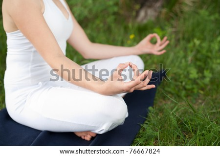 Meditation in nature - Cute young girl meditates outdoor on a green grass field in park