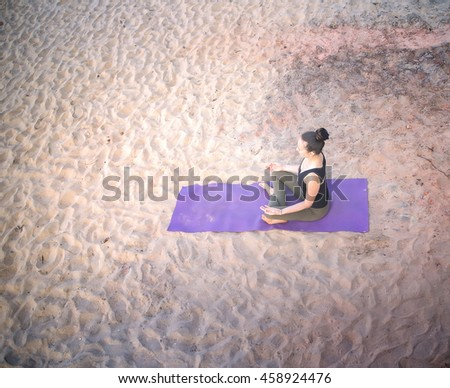 meditation on beach girls yoga trainer at home yoga. Shot from the top among the beach with light sand