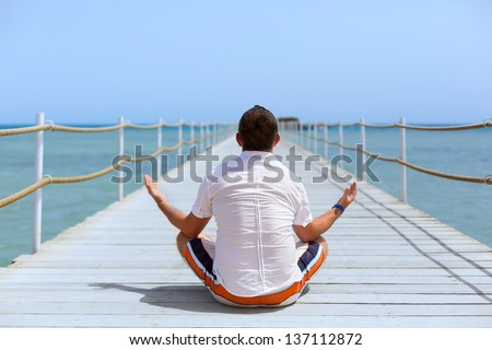 Meditation  on the pier of Red Sea, Egypt - stock photo
