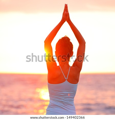 Meditation Yoga woman meditating at beach sunset or sunrise relaxing in yoga pose. Serene relaxed female yoga instructor in calm nature sea scene. From Big Island, Hawaii, USA. - stock photo