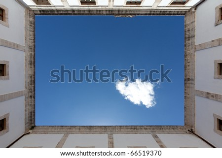 mediterian courtyard with blue sky and single cloud - stock photo