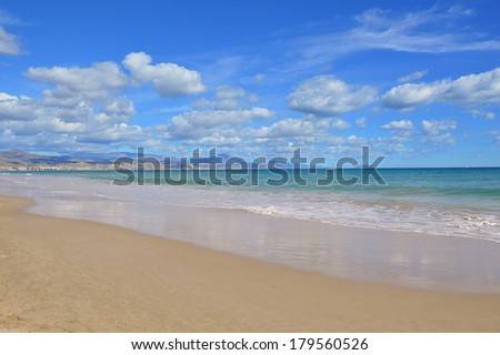 Mediterranean Beach in San Juan Playa in costa blanca Alicante Spain Europe Puig Campana (Peak Mountain in Castellano Spanish)  mountain in the far distance. Benidorm along the far distant coastline.