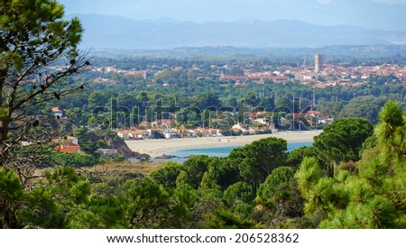 Mediterranean beach of the Racou in Argeles-sur-Mer with the village in background, Roussillon, Pyrenees Orientales, France - stock photo