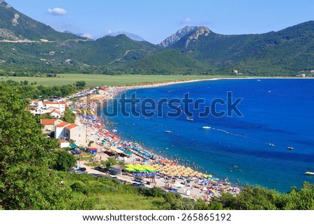 Mediterranean beach surrounded by distant mountains - stock photo