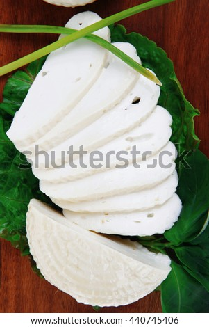mediterranean dairy  : fresh raw white soft greek feta cheese round and slices on wooden plate isolated over white background - stock photo