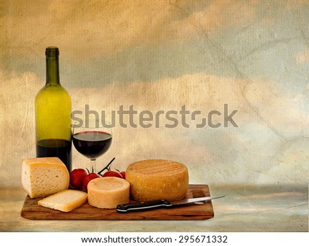 Mediterranean diet, lifestyle.  Red wine, cheese and tomatoes in rustic setting, warm light. - stock photo