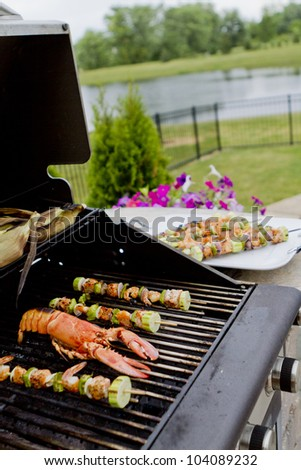 Mediterranean fish shish kebabs and lobsteron the BBQ almost ready. Hungry people waiting. - stock photo