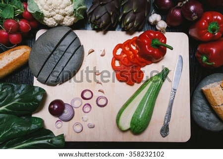Mediterranean foods on the table. Chopped vegetables. Black bread with carbon, integral bread, onion, garlic, zucchini, peppers, cauliflower, chard, radishes and artichokes. - stock photo