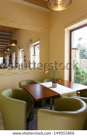 Mediterranean interior - a wooden lunch table with khaki armchairs