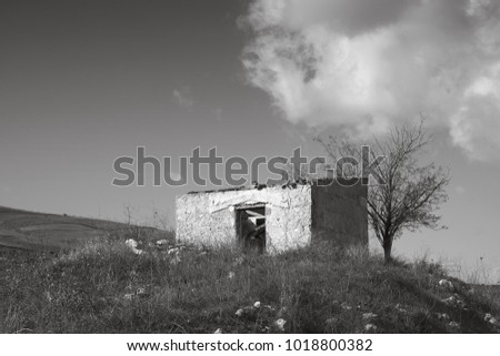 Mediterranean landscape in black and white. Landscapes of southern Italy, Sicily. Rustic cottage abandoned in the countryside in the hills.