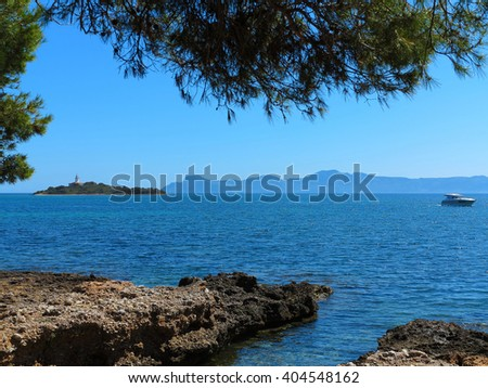 mediterranean landscape with little island, lighthouse and motorboat - stock photo