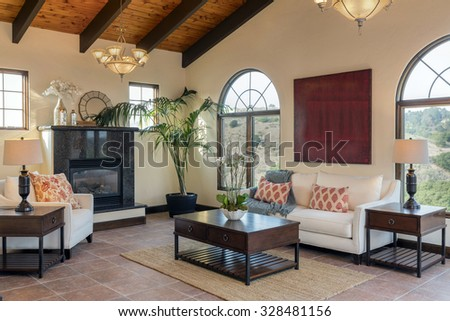 Mediterranean living room with beige walls, sofa, sectionals, wooden stands, fireplace place, coffee table and wooden ceiling. - stock photo