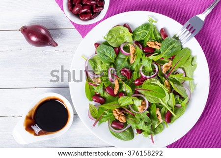 Mediterranean low calories red beans salad with mix of lettuce leaves. red onion rings, walnuts on a white dish on a wood table, close-up, top view - stock photo