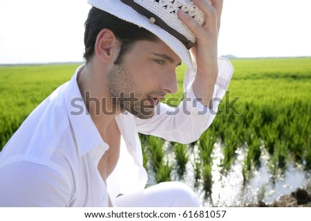 Mediterranean man portrait white hat in green meadow rice field