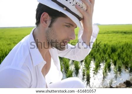 Mediterranean man portrait white hat in green meadow rice field - stock photo