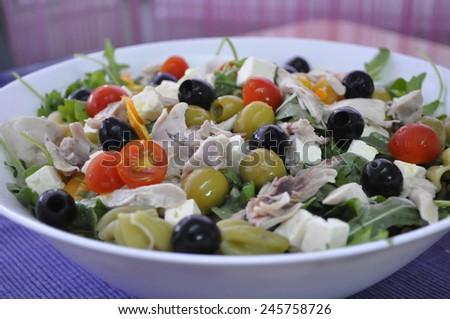 Mediterranean salad with chicken, cheese, pasta and black olives - stock photo