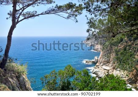 Mediterranean sea foam rocky shore under sky - stock photo