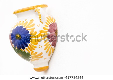 mediterranean single painted decorative pot. Shot in shallow depth of field in the colors of yellow,blue green and purple on a white wall background, with room for text copy space ideal for notice   - stock photo