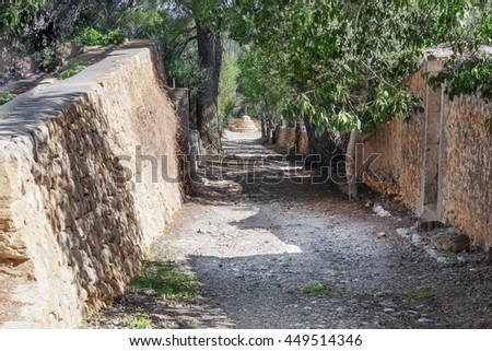 Mediterranean small road in the summer with a stone wall, texture Backgrounds. - stock photo