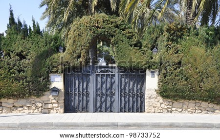 Mediterranean Spanish Style Home Gate Entrance with Landscaped Evergreen Shrubs Palm Trees in the community of Valencia and the province of Alicante Spain Europe - stock photo