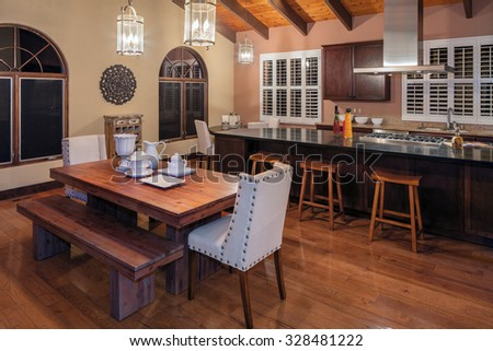 Mediterranean Spanish style wooden kitchen with huge kitchen island, wooden dining table and bar chairs / stools at night. - stock photo