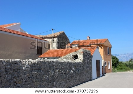 Mediterranean street view with mountains on the far background. End of street in small Adriatic town. Limestone fences, red tiled roofs for summer travels. Adriatic southern seaside street view. - stock photo